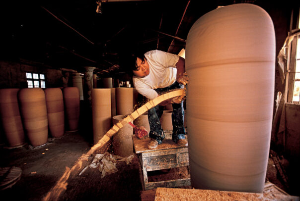 A worker trims a gian pot.