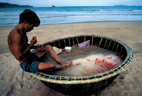 boy fixing nets on the beach