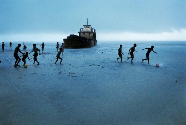 children playing football on the beach near a ship