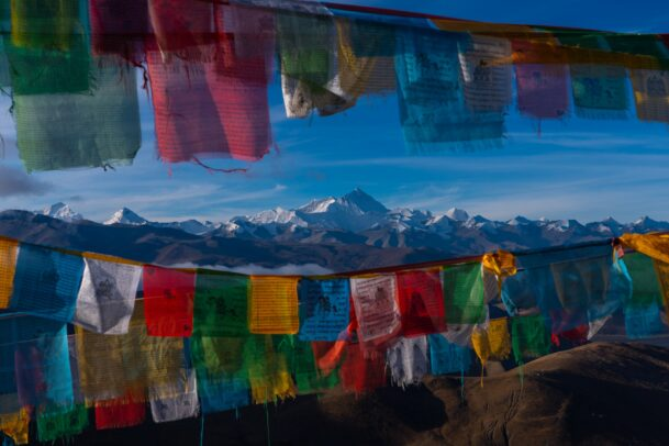 colorful flags in front of the tibetan mountains