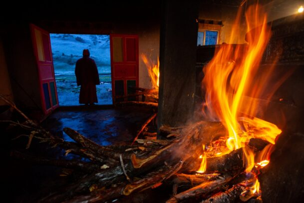burning fire and a tibetan monk in the background