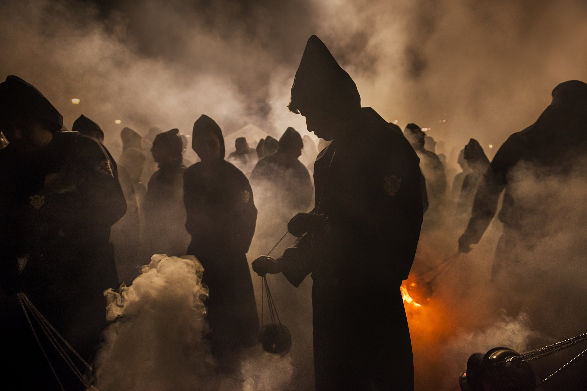 figures through smoke and fire of a catholic procession in Guatemala